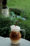 Cool ice caramel macchiato coffee on rough wooden table in topical garden. Stock Images
