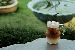 Cool ice caramel macchiato coffee on rough wooden table in topical garden. Royalty Free Stock Photography