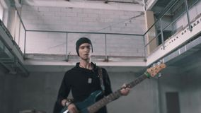 Cool instrumental Duo. Bass guitarist and drummer in the background. Musicians play in an unfinished room similar to a warehouse stock video footage