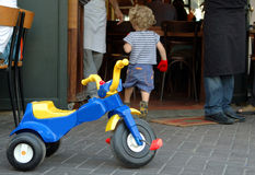 Cool kid. Running into a restaurant after parking his tricycle in the front stock images