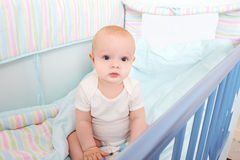 Cool kid sitting in baby bed and looks. Royalty Free Stock Images
