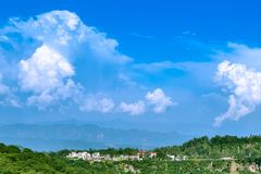 Cool landscape with blue sky and amazing white clouds. Beautiful view of hills with blue sky and white clouds on background, mountain covered with mist stock images