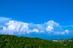 Cool landscape with blue sky and amazing white clouds. Beautiful view of hills with blue sky and white clouds on background, mountain covered with mist royalty free stock images