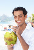 Cool latin guy drinking coconut water at beach Royalty Free Stock Photos