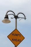 Cool light post and sign. Cool looking light post with a strange street sign attached, Humps Ahead Royalty Free Stock Photos