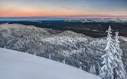 Sunrise over Cascade Mountain Valley. Winter Sunrise Illuminates Snowy Mountain Valley Stock Photo