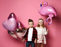Cool little boy with color heart balloons and pretty little girl with flamingo balloon came together at the party. On pink background royalty free stock photography