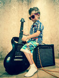 Cool little boy posing with electric guitar. Cool little boy posing with electric guitar like a rock singer Royalty Free Stock Photo