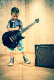 Cool little boy posing with electric guitar. Cool little boy posing with electric guitar like a rock singer Royalty Free Stock Photography