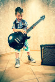 Cool little boy posing with electric guitar. Cool little boy posing with electric guitar like a rock singer Stock Image