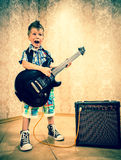 Cool little boy posing with electric guitar. Royalty Free Stock Image
