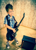 Cool little boy posing with electric guitar. Cool little boy posing with electric guitar like a rock singer Royalty Free Stock Photos