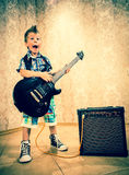 Cool little boy posing with electric guitar. Stock Photo