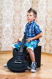 Cool little boy posing with electric guitar. Royalty Free Stock Photo