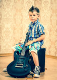 Cool little boy posing with electric guitar. Cool little boy posing with electric guitar like a rock singer Stock Photo
