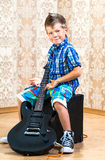 Cool little boy posing with electric guitar. Cool little boy posing with electric guitar like a rock singer Stock Images
