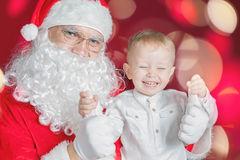 Cool little boy and Santa Claus at Christmas holiday Stock Images