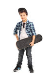 Cool little kid holding a skateboard. Full length portrait of a cool little kid holding a skateboard and looking at the camera isolated on white background Stock Images