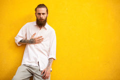 Cool looking bearded men lying on yellow wall Stock Photography