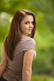 Cool looking beautiful brunette woman. A cool looking beautiful brunette woman in her twenties standing in a park and looking into the camera stock images
