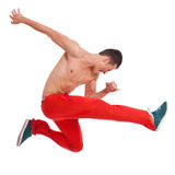 Cool looking dancer makes a difficult jump. Over white Royalty Free Stock Photography