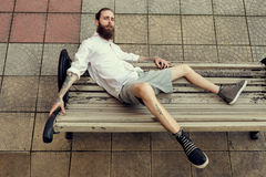 Cool looking guy with tatoos and long beard sitting on chair pos. Ing at camera and posing in fashion style. Nonconformism and hipster Stock Photo