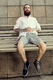Cool looking guy with tatoos and long beard sitting on chair. And posing in fashion style. Nonconformism and hipster Royalty Free Stock Photo