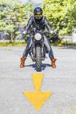 Cool looking motorcycle rider on custom made scrambler style cafe racer on the road with an arrow sign stock photo
