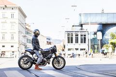Cool looking motorcycle rider on custom made scrambler style cafe racer Stock Photography