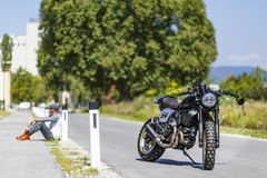 Motorcycle rider sitting near custom made scrambler style cafe r royalty free stock photo