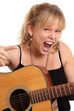 Cool looking woman with acoustic guitar. Screaming female holding an acoustic guitar doing the heavy metal sign. White background stock photo