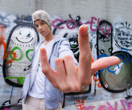 Cool-looking young man in front of graffiti Royalty Free Stock Photos