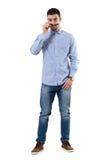 Cool macho smart casual man taking off sunglasses staring at camera. Stock Photography