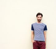 Cool male fashion model with beard leaning against wall Stock Photo