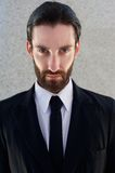 Cool male fashion model with beard posing in black suit and tie Stock Photography