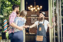 Cool hairstylist giving a fist bump to a happy customer at the door of a salon stock photography