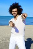 Cool male model on beach smiling and pointing fingers posing Stock Photography