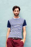 Cool male model in striped shirt leaning against wall Stock Image