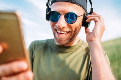 Cool man in baseball cap, wireless headphones and blue sunglasses browsing in his mp3 player playlists smartphone device and royalty free stock image