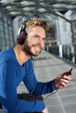 Cool man with beard smiling with headphones and mobile phone. Portrait of a cool man with beard smiling with headphones and mobile phone Royalty Free Stock Images