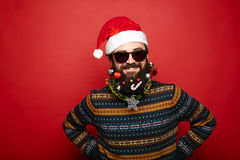 Cool man dressed as Santa Claus over red background Royalty Free Stock Images
