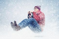 Cool man driver in round glasses, red sweater, and hat, with steering wheel. Winter, snow, blizzard.  Stock Photography