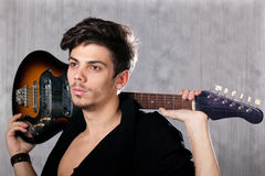 Cool man with electric guitar. Concept for rock concert. Artistic image of young cool man  with electric guitar. Image taken in studio with backlight and lens Royalty Free Stock Images