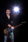 Cool man with electric guitar. Concept for rock concert. Artistic image of young cool man  playing electric guitar. Image taken in studio with back light and Stock Photo