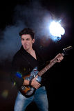 Cool man with electric guitar. Concept for rock concert. Artistic image of young cool man  playing electric guitar. Image taken in studio with back light and Stock Image