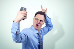 Cool man in funny cardboard glasses makes a smartphone selfie Royalty Free Stock Photos