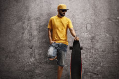 Cool man holding a longboard. Cool man leaning against a rusty concrete wall and holding a longboard Stock Image