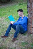 Cool man reading a book next a tree Stock Photo