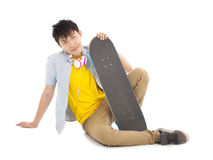 Cool man sitting and holding a skateboard Stock Image
