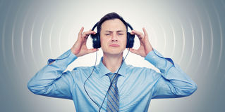 Cool man in tie listening to music on headphones Royalty Free Stock Images